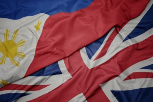 waving colorful flag of great britain and national flag of philippines.